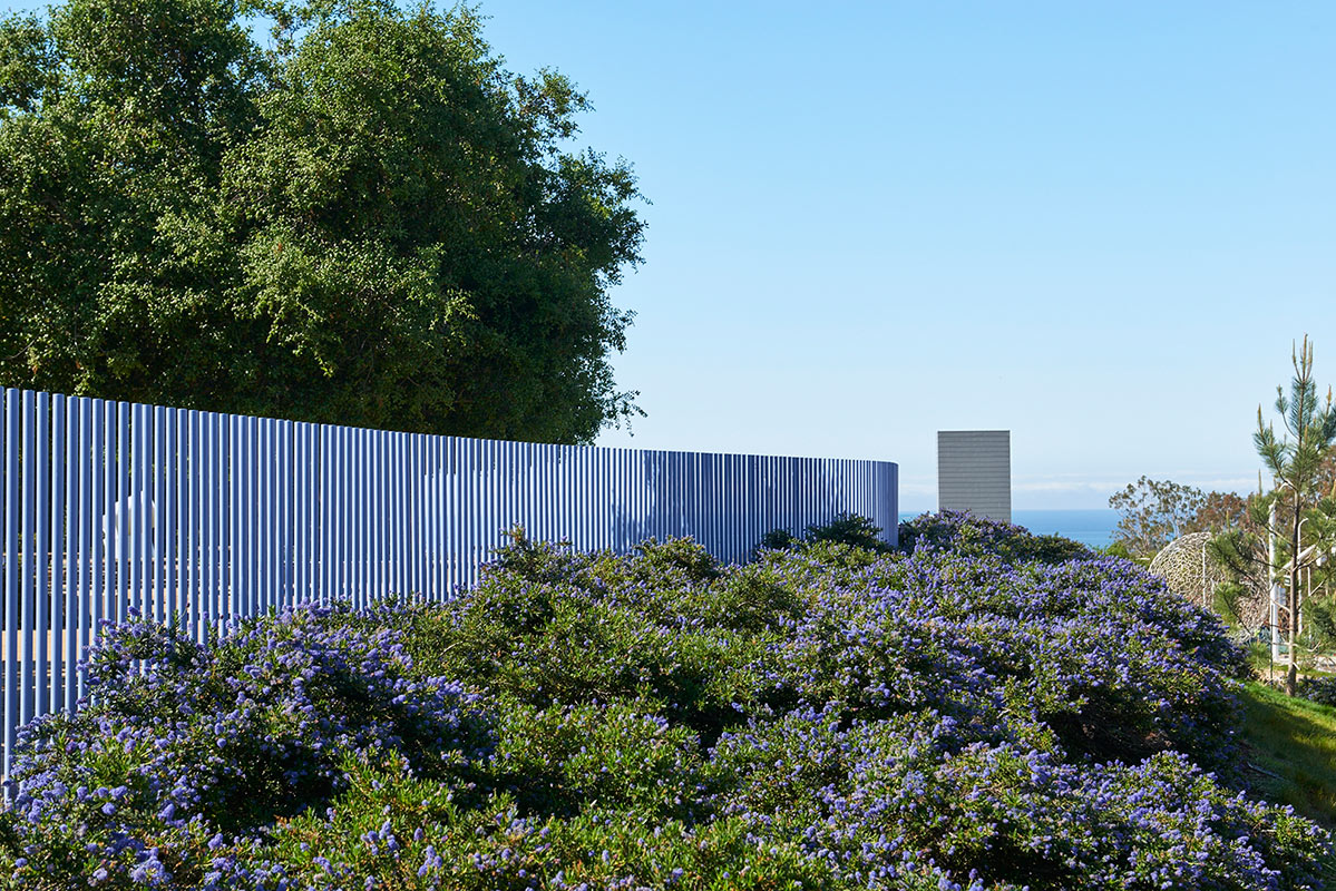The sinuous dog park fence within the garden is a landmark above to people passing by